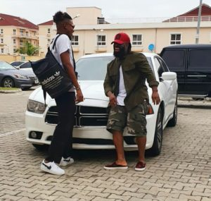 Timaya pictured with one of his luxury cars